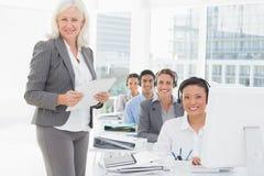 Lächelnde Geschäftsfrau, die Kamera während Arbeitsteam unter Verwendung des Computers betrachtet Stockfotografie
