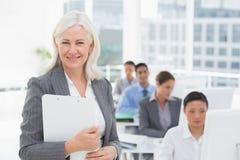 Lächelnde Geschäftsfrau, die Kamera während Arbeitsteam unter Verwendung des Computers betrachtet Lizenzfreie Stockfotos