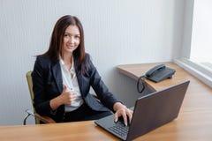 Lächelnde Geschäftsfrau, die an Laptop arbeitet und oben Daumen schiebt stockbilder