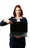 Lächelnde Geschäftsfrau, die Laptop hält und auf ihn zeigt lizenzfreies stockfoto