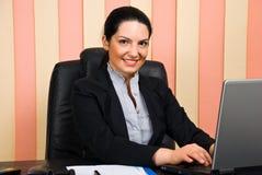 Lächelnde Geschäftsfrau, die Laptop im Büro verwendet Stockfotos