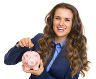 Lächelnde Geschäftsfrau, die Münze in Sparschwein setzt Stockfoto