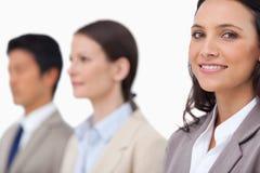 Lächelnde Geschäftsfrau, die nahe bei Kollegen steht Stockfotos