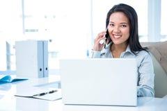 Lächelnde Geschäftsfrau, die am Schreibtisch anruft Stockbild