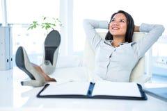 Lächelnde Geschäftsfrau, die sich entspannt Stockfoto