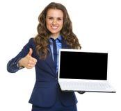 Lächelnde Geschäftsfrau, die sich Laptopleeren bildschirm und -daumen zeigt Stockfoto