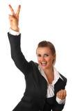 Lächelnde Geschäftsfrau, die Sieggeste zeigt Stockbilder