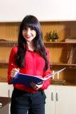 Lächelnde Geschäftsfrau in einer roten Bluse mit einem Ordner stockfotografie