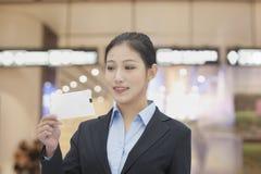 Lächelnde Geschäftsfrau am Flughafen, der Flugschein betrachtet Stockfoto