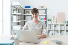 Lächelnde Geschäftsfrau im Büro stockbild