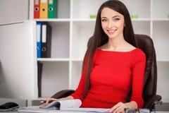 Lächelnde Geschäftsfrau im rotem Kleidersitzen und in Schreiben somethin lizenzfreie stockbilder