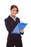 Lächelnde Geschäftsfrau mit blauem Klemmbrett Stockfotografie