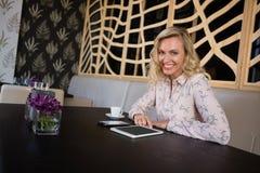 Lächelnde Geschäftsfrau mit digitaler Tablette und dem Handy, die im Café sitzt Lizenzfreie Stockbilder