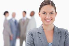 Lächelnde Geschäftsfrau mit Kollegen hinter ihr Lizenzfreies Stockbild
