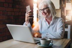 Lächelnde Geschäftsfrau sitzt bei Tisch vor Laptop und Lizenzfreie Stockfotografie