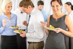 Lächelnde Geschäftsfrau während des Firmamittagessenbuffets Stockfoto