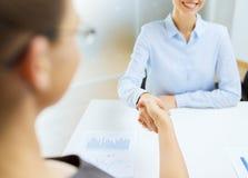 Lächelnde Geschäftsfrau zwei, die Hände im Büro rüttelt Stockfotos