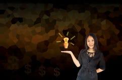 Lächelnde Geschäftsfrauen Asien-Frauen, die Glühlampe in smal darstellen Stockbilder