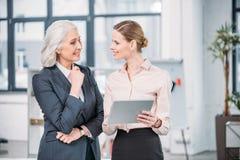 Lächelnde Geschäftsfrauen, die digitale Tablette verwenden und im Büro sprechen Lizenzfreies Stockfoto