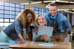 Lächelnde Geschäftsleute bei der Diskussion über Tablet-Computer stockfotos