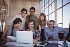 Lächelnde Geschäftsleute, die über Laptop im Büro sich besprechen lizenzfreies stockfoto