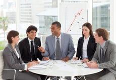 Lächelnde Geschäftsleute, die einen Haushaltsplan behandeln Lizenzfreie Stockfotografie