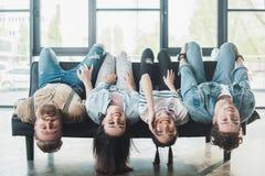 Lächelnde Geschäftsleute, die herum auf Sofa in modernem täuschen lizenzfreie stockfotografie
