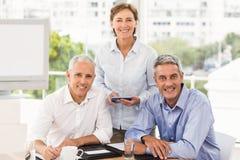 Lächelnde Geschäftsleute, die Kamera betrachten Lizenzfreie Stockfotos