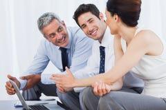 Lächelnde Geschäftsleute, die mit ihrem Laptop auf Sofa arbeiten Lizenzfreie Stockfotos