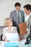 Lächelnde Geschäftsleute im Büro Stockbilder