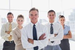 Lächelnde Geschäftsleute mit den Armen kreuzten in ihrem Büro stockfoto