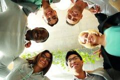 Lächelnde Geschäftsleute mit ihren Köpfen zusammen Lizenzfreie Stockfotografie