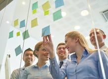 Lächelnde Geschäftsleute mit Markierung und Aufklebern Lizenzfreies Stockfoto