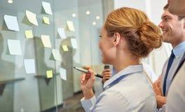 Lächelnde Geschäftsleute mit Markierung und Aufklebern Lizenzfreie Stockbilder
