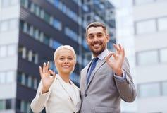 Lächelnde Geschäftsmänner, die über Bürogebäude stehen Stockbild