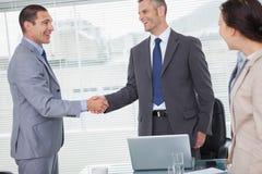 Lächelnde Geschäftsmänner, die Hände stehen und rütteln Stockfotos