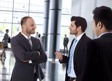 Lächelnde Geschäftsmänner, die innerhalb des Bürogebäudes sprechen Stockfotografie