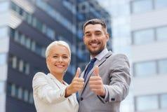 Lächelnde Geschäftsmänner, die sich Daumen zeigen Stockbild