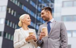 Lächelnde Geschäftsmänner mit Papierschalen draußen Stockbild