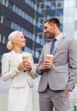 Lächelnde Geschäftsmänner mit Papierschalen draußen Stockbilder