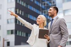 Lächelnde Geschäftsmänner mit Tabletten-PC draußen Stockfoto