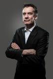 Lächelnde Geschäftsmann-Arme falteten sich auf Grau Stockfotos