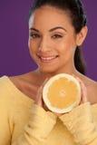 Lächelnde geschnittene Orange der Frau Holding Lizenzfreie Stockfotos