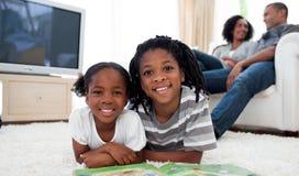 Lächelnde Geschwister, die das Lügen auf dem Fußboden lesen Stockfoto