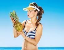Lächelnde gesunde Frau in der Badebekleidung auf dem Strand, der Ananas hält Stockbilder