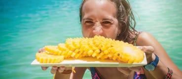Lächelnde gesunde Frau im Badeanzug auf dem Strand mit Ananas Lizenzfreies Stockfoto