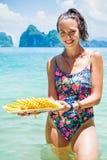 Lächelnde gesunde Frau im Badeanzug auf dem Strand mit Ananas Stockbilder
