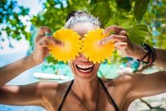 Lächelnde gesunde Frau im Badeanzug auf dem Strand mit Ananas Stockbild