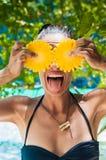 Lächelnde gesunde Frau im Badeanzug auf dem Strand mit Ananas Lizenzfreie Stockfotografie