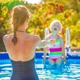 Lächelnde gesunde Mutter und Kind beim Swimmingpoolspielen Stockfotos